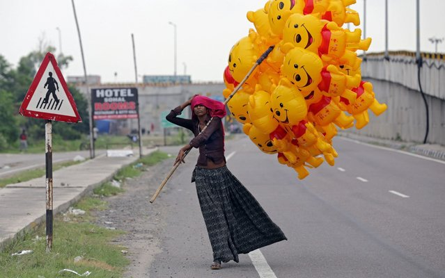 A vendor adjusts her scarf as she sells Winnie the Pooh cartoon-shaped balloons on a highway during the weekend lockdown in Amritsar, India, 30 August 2020. Another lockdown was imposed by the state government to control the spread of novel coronavirus which causes the Covid19 disease. (Photo by Raminder Pal Singh/EPA/EFE/Rex Features/Shutterstock)