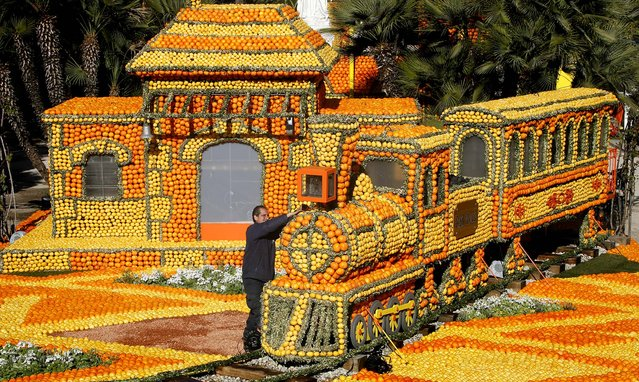 A worker puts the finishing touches on a train made with lemons and oranges during the 80th Lemon festival in Menton on February 15, 2013. (Photo by Lionel Cironneau/Associated Press)