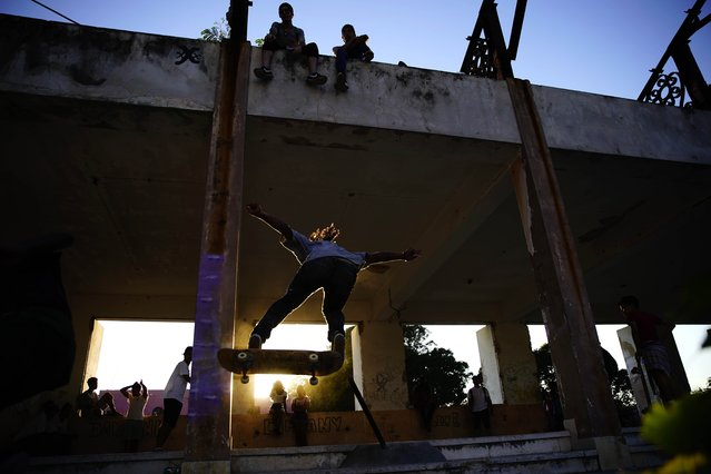 In this January 11, 2018 photo, a skater jumps a ramp during the inauguration of a new recreational space for skateboarders, created in an abandoned gym at the Educational complex Ciudad Libertad, a former military barracks that the late Fidel Castro turned into a school complex after the revolution in Havana, Cuba. Foreign skateboard enthusiasts supply their Cuban counterparts with boards and other equipment. (Photo by Ramon Espinosa/AP Photo)