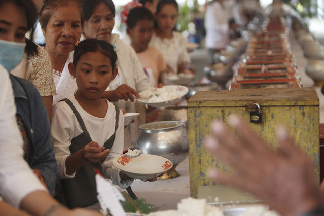 Local residents offer foods during a ceremony to celebrate Pchum Ben, or Ancestors' Day, at a Buddhist pagoda of Tang Krasang, on the outskirts of Phnom Penh, Cambodia, Thursday morning, September 3, 2020. Cambodians on Thursday began celebrating their traditional 15-day Pchum Ben festival aimed at paying respect to deceased relatives. (Photo by Heng Sinith/AP Photo)