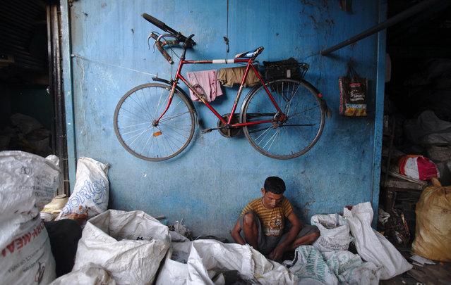 A man works at a metal parts recycling factory in Mumbai, October 12, 2012. (Photo by Vivek Prakash/Reuters)
