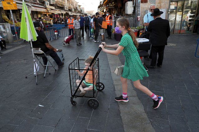 A girl pushes a trolley with a toddler in it in a main market ahead of Yom Kippur, the Jewish Day of Atonement as Israel is set to tighten its second nationwide coronavirus disease (COVID-19) lockdown amid a rise in infections, later today, in Jerusalem on September 25, 2020. (Photo by Ronen Zvulun/Reuters)
