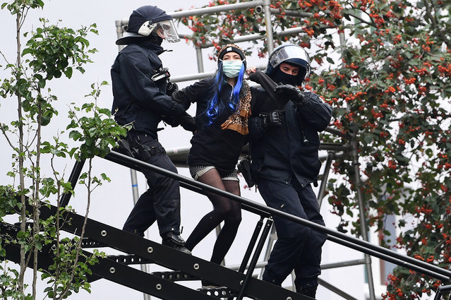 """Police officers in action during the eviction of the """"Liebig 34"""" squat, at Friedrichshain district in Berlin, Germany, 09 October 2020. A local court ruled in favor of the eviction of the self-declared """"anarcha-queer feminist"""" house project at Liebig street 34 in June 2020. The house project is considered a stronghold of the left-wing scene in the German capital. (Photo by Filip Singer/EPA/EFE)"""