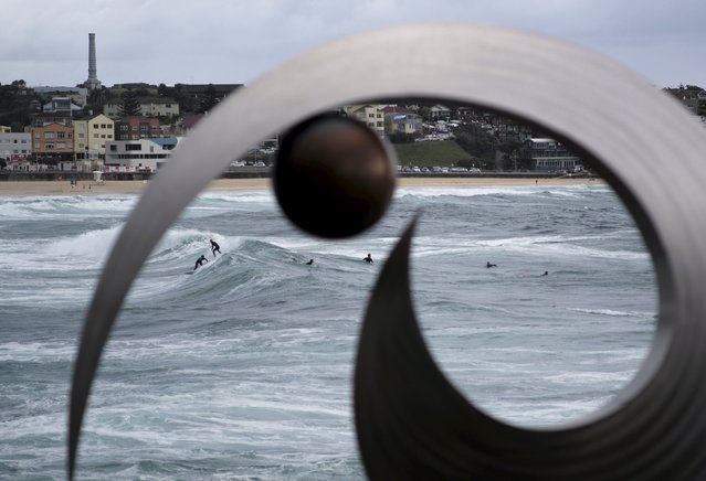 Surfers ride the waves off Sydney's Bondi Beach behind the stainless steel and bronze sculpture by Australian artist Ben Fasham entitled ' BJF13' during the 19th annual Sculptures by the Sea exhibition in Sydney, October 23, 2015. (Photo by Jason Reed/Reuters)