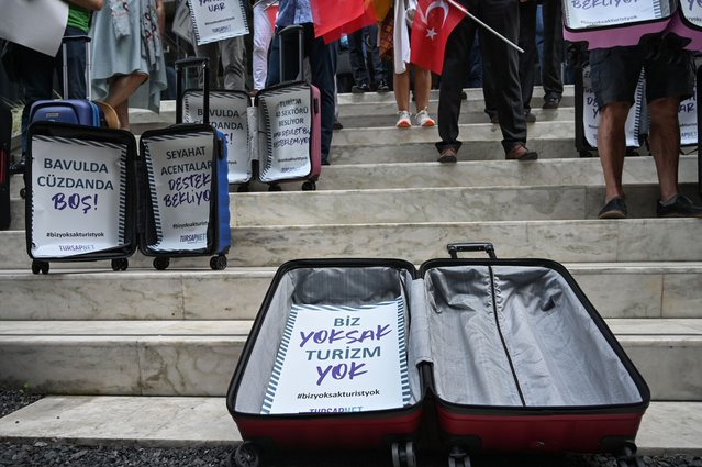 """Travel agency owners display empty suitcases after a press conference demanding government's financial support for the tourism agencies as the spread of the coronavirus disease (COVID-19) continues, placards reads """"travel agencies expect support-our pockets and suitcases are empty- If there is no agencies, there is no Tourism"""" in Istanbul on October 6, 2020. (Photo by Ozan Kose/AFP Photo)"""