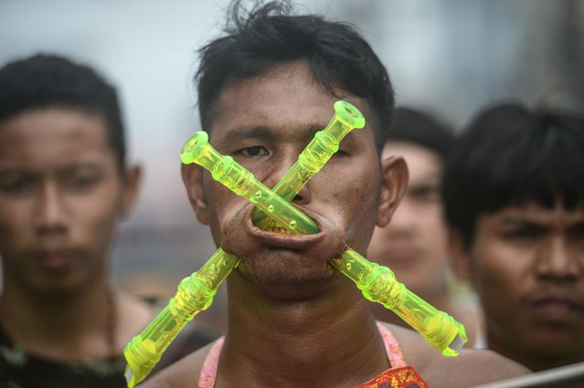 A devotee of the Nine Emperor Gods parades through the town of Phuket with recorders pierced through his cheeks during the annual Phuket Vegetarian Festival in the southern province of Phuket on October 3, 2016. (Photo by Lillian Suwanrumpha/AFP Photo)