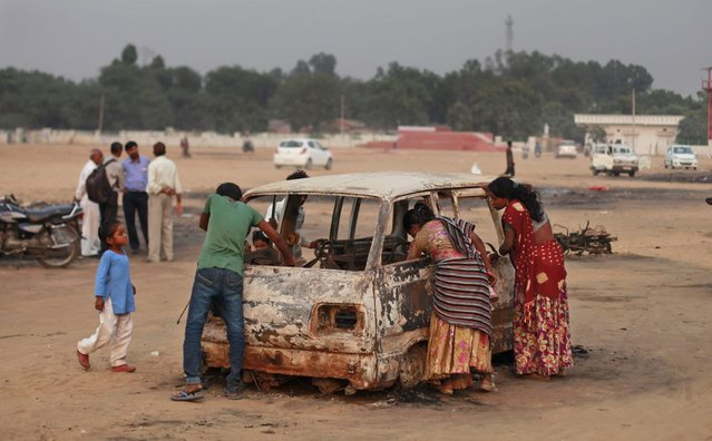 Indian waste pickers look for reusables from the debris of a damaged vehicle at a fair ground where a massive fire Tuesday evening gutted down a temporary fire crackers market set up for the Diwali festival in Faridabad, a suburb of New Delhi, India, Wednesday, October 22, 2014. According to local news reports more than two hundred temporary shops were gutted down in the fire but no one was hurt. (Photo by Altaf Qadri/AP Photo)