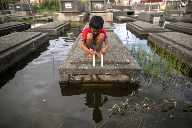 A boy attempts to keep a candle lit in a flooded cemetery following Typhoon Molave, in Masantol, Pampanga, Philippines, October 27, 2020. (Photo by Eloisa Lopez/Reuters)
