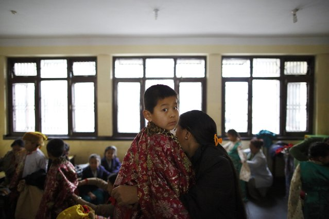 A Tibetan boy gets help from his mother as he gets dressed for a function organised by the Tibetan Refugee Community in Nepal, commemorating the 25th Anniversary of the Nobel Peace Prize conferment to exiled Tibetan spiritual leader Dalai Lama and the 66th International Human Rights Day in Kathmandu December 10, 2014. (Photo by Navesh Chitrakar/Reuters)