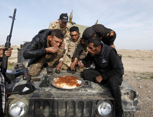 Members of Iraqi security forces and Shiite fighters eat on their vehicle on the outskirts of Baiji, north of Baghdad December 8, 2014. (Photo by Ahmed Saad/Reuters)