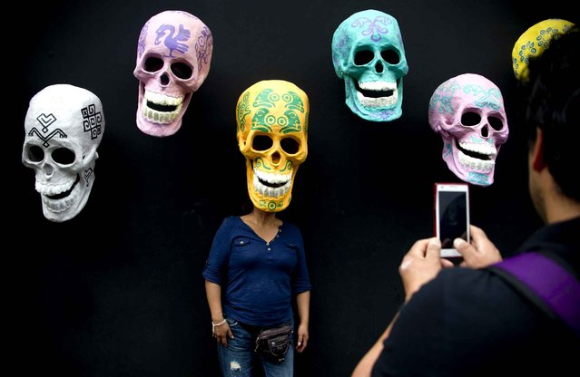 A woman poses for pictures with skulls made of cardboard placed on an altar next to the San Francisco church in Mexico City during the celebration of All Souls Day on November 2, 2015. (Photo by Yuri Cortez/AFP Photo)