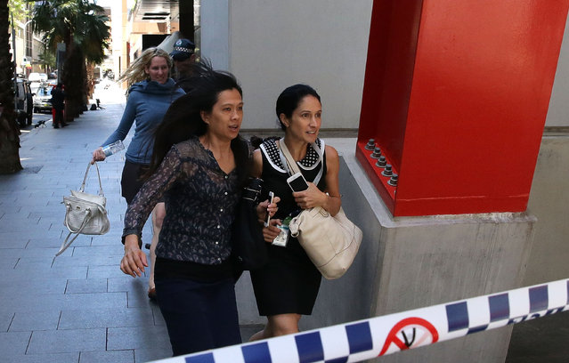 Ladies rush through Philip St past armed police at Lindt Cafe, Martin Place on December 15, 2014 in Sydney, Australia.  Police attend a hostage situation at Lindt Cafe in Martin Place. (Photo by Mark Metcalfe/Getty Images)