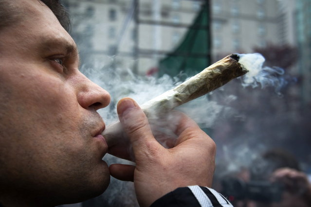 A man smokes marijuana at the Vancouver Art Gallery during the annual 4/20 day, which promotes the use of marijuana, in Vancouver, British Columbia April 20, 2013. (Photo by Ben Nelms/Reuters)