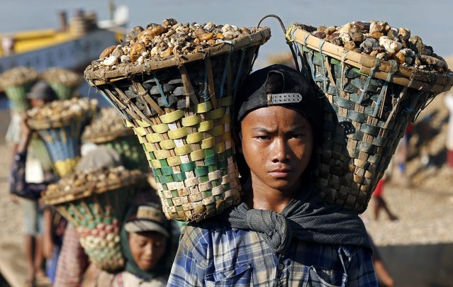 A Myanmar child laborer carries baskets loaded with gravel used for construction on his shoulders in Yangon, Myanmar, 06 November 2015. The new minimum wage of 3600 Kyats (2.80 dollars) for a standard eight-hour work day across all sectors and industries took effect in September. (Photo by Rungroj Yongrit/EPA)