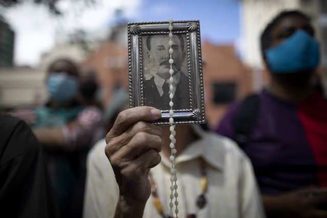 "A devotee of late Venezuelan Dr. José Gregorio Hernández holds up his picture and a rosary outside La Candelaria church where he is buried in Caracas, Venezuela, Monday, October 26, 2020. The remains of the doctor popularly known as the ""Saint of the Poor"" were exhumed today in a private ceremony inside the church as part of a Vatican request for the beatification process of the first Venezuelan layperson. (Photo by Ariana Cubillos/AP Photo)"