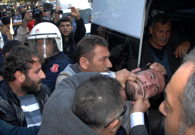 Plain clothed police officers detain a man who was trying to set up a tent to mourn and commemorate the fighters killed in Syrian city of Ayn al-Arab or Kobani, in southern Turkish city of Adana, Turkey, Monday, December 15, 2014.(Photo by AP Photo/Hurriyet)