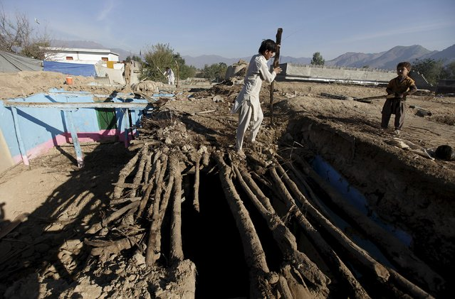 A man dismantles a section of his house which was damaged by the earthquake in Bazarak village in Dir district, Pakistan, October 29, 2015.The powerful earthquake struck a remote area of northeastern Afghanistan on Monday, shaking the capital Kabul, as shockwaves were felt in northern India and inPakistan's capital, where hundreds of people ran out of buildings as the ground rolled beneath them. (Photo by Faisal Mahmood/Reuters)