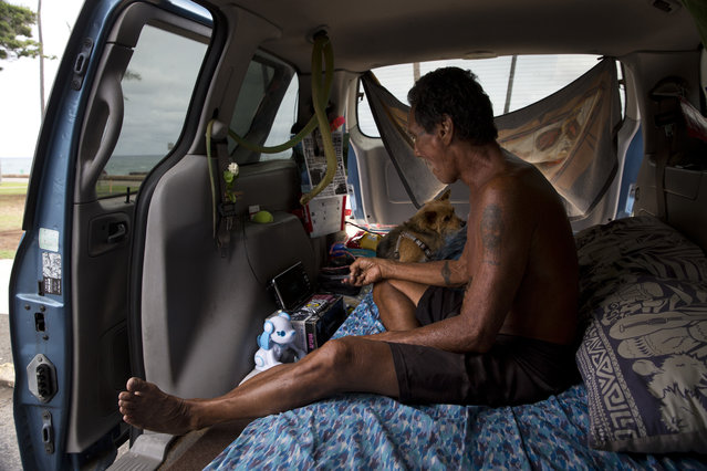 In this Monday, August 24, 2015 photo, Dexter Lii, a retired surf instructor, and his dog sit in a minivan in Kakaako Waterfront Park in Honolulu. The number of homeless people in Hawaii grew over the past five years, and the state's population of unsheltered families ballooned 46 percent from 2014 to 2015, said Scott Morishige, state coordinator on homelessness. (Photo by Jae C. Hong/AP Photo)