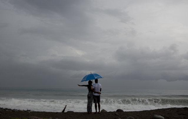 A couple watches the sea under the rain in Kingston, Jamaica, Sunday, October 2, 2016. (Photo by Eduardo Verdugo/AP Photo)