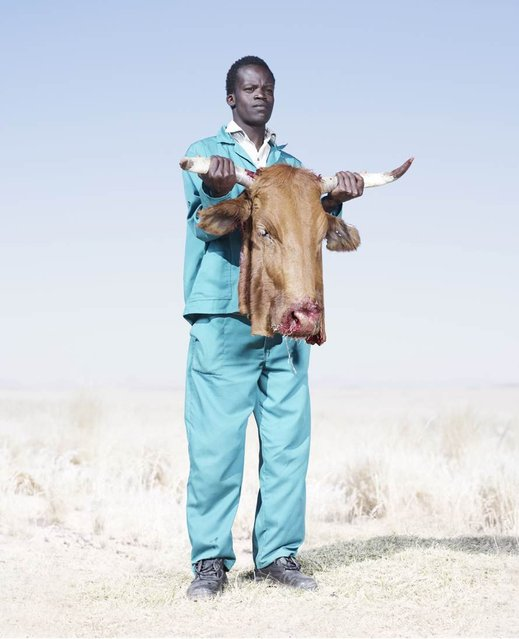 A Herero man holds the head of a freshly butchered cow, killed to supply meat for a funeral, 2012. (Photo by Jim Naughten, courtesy of Klompching Gallery, New York)