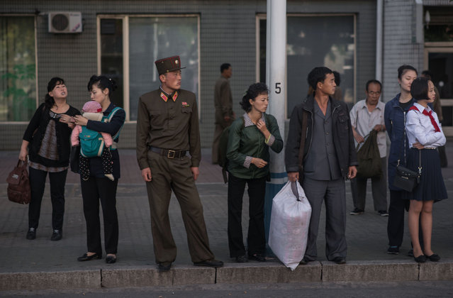 In this picture taken on September 29, 2016 commuters wait for a bus during the morning rush hour in Pyongyang. (Photo by Ed Jones/AFP Photo)