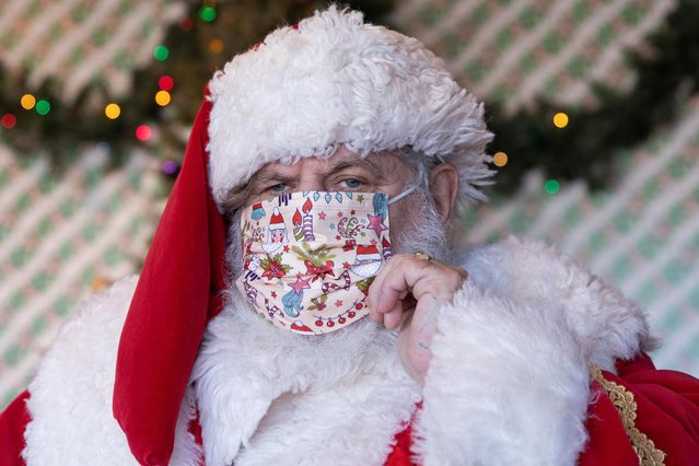 Dana Friedman, a trial lawyer who has spent 6 months of each year growing out his beard for his annual appearances as Santa Claus since 2001, adjusts his mask before greeting a child at the Bay Terrace Shopping Center in Queens, New York City, December 6, 2020. (Photo by Caitlin Ochs/Reuters)