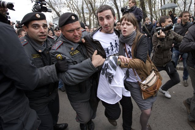 Russian police officers detain an unidentified man during a protest rally in Bolotnaya Square in Moscow, Russia, Monday May 6, 2013. Up to 20,000 Russian opposition supporters gathered for a protest on Monday, venting anger against the Kremlin and demanding the release of political prisoners. The protest came exactly one year after a demonstration a day before President Vladimir Putin's third presidential inauguration on the same square near the Kremlin ended in violent clashes between demonstrators and police. (AP Photo/Ivan Sekretarev)