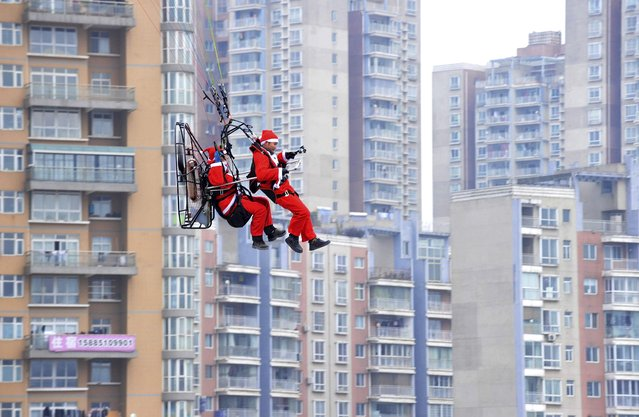 Members of a local powered parachute club wearing Santa Claus costumes fly past residential buildings to drop presents to pedestrians during a promotional event celebrating Christmas in Guiyang, Guizhou province December 24, 2014. (Photo by Reuters/Stringer)