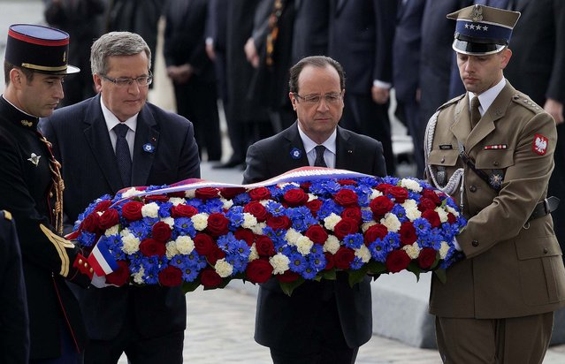 Polish President Bronislaw Komorowski and French President Francois Hollande, flanked by French and Polish soldiers, lay a wreath at the Tomb of the Unknown Soldier beneath the Arc de Triomphe in Paris during Wednesday's  ceremony marking the 68th anniversary of the end of World War II in Europe. (Photo by Michel Euler/Associated Press)