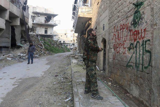 "A ""Free Syrian Army"" fighter sprays graffiti on a wall prior to the new year in Aleppo December 31, 2014. (Photo by Jalal Al-Mamo/Reuters)"
