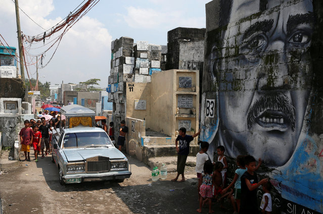 Families and friends walk behind the hearse transporting the coffin of Vicente Batiancila, whom police said was among five victims of drug related killings three weeks ago, during his funeral in Navotas, Metro Manila in the Philippines, October 23, 2016. (Photo by Erik De Castro/Reuters)