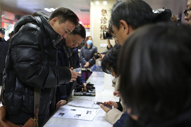 People try to identify their relatives from some of the victims' pictures at a hospital after a stampede incident during a New Year's celebration on the Bund, central Shanghai January 1, 2015. (Photo by Aly Song/Reuters)