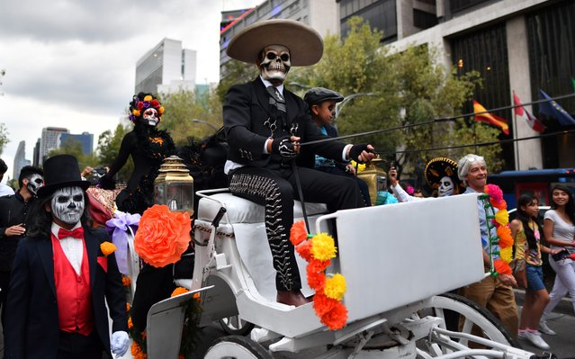 "People fancy dressed as ""Catrina"" take part in the ""Catrinas Parade"" along Reforma Avenue, in Mexico City on October 23, 2016. (Photo by Yuri Cortez/AFP Photo)"