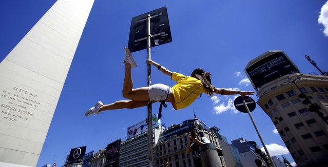 """A dancer performs in the street to promote the """"Miss Pole Dance Sudamerica 2010"""" competition to be held Saturday in Buenos Aires, Argentina. (Photo by Natacha Pisarenko/Associated Press)"""