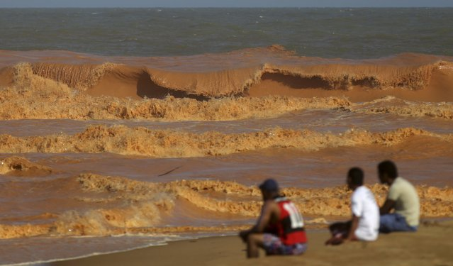 Men look on from the banks of Rio Doce (Doce River), which was flooded with mud after a dam owned by Vale SA and BHP Billiton Ltd burst, as the river joins the sea on the coast of Espirito Santo in Regencia Village, Brazil, November 22, 2015. (Photo by Ricardo Moraes/Reuters)