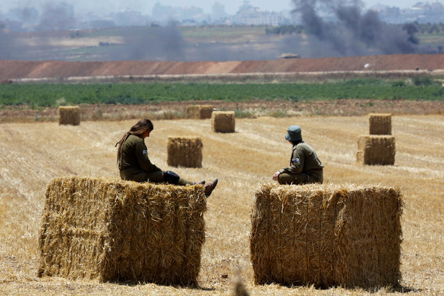 Israeli soldiers sit on bales of hay in a field overlooking Gaza, on the Israeli side of the border between Israel and the Gaza Strip May 15, 2018. (Photo by Amir Cohen/Reuters)