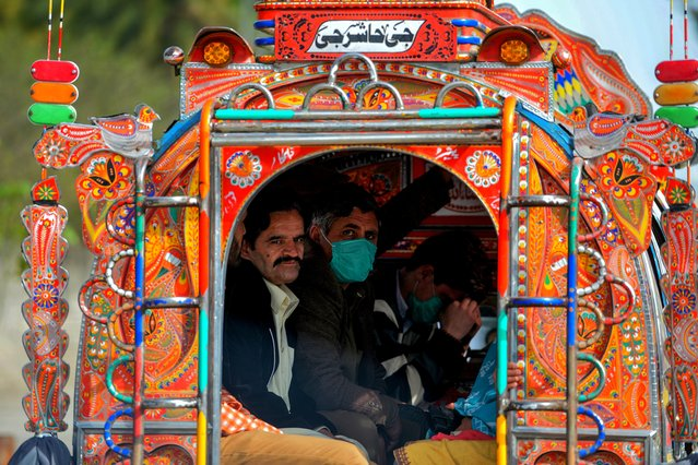 Residents wearing facemasks as a preventive measure against the spread of the COVID-19 coronavirus sit in a passenger pick-up on a street in Rawalpindi on March 13, 2020. (Photo by Aamir Qureshi/AFP Photo)