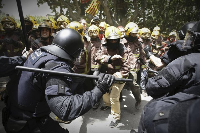 Riot police charge at firefighters during a protest against austerity measures in front of the Catalunya Parliament in Barcelona, Spain, Wednesday, May 29, 2013. The European Union moved away from its focus on tough austerity Wednesday when it gave France, Spain and four other member states more time to bring their budget deficits under control to support their economies. (Photo by Paco Serinelli/AP Photo)