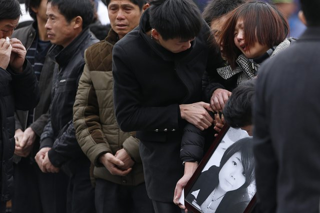 Relatives cry as they hold a picture of a victim at a memorial ceremony for people who were killed in a stampede incident last Wednesday during a New Year's celebration on the Bund, in Shanghai, January 6, 2015. Chinese state media and the public criticised the government and police on Friday for failing to prevent the stampede in Shanghai that killed 36 people and dented the city's image as modern China's global financial hub. (Photo by Aly Song/Reuters)