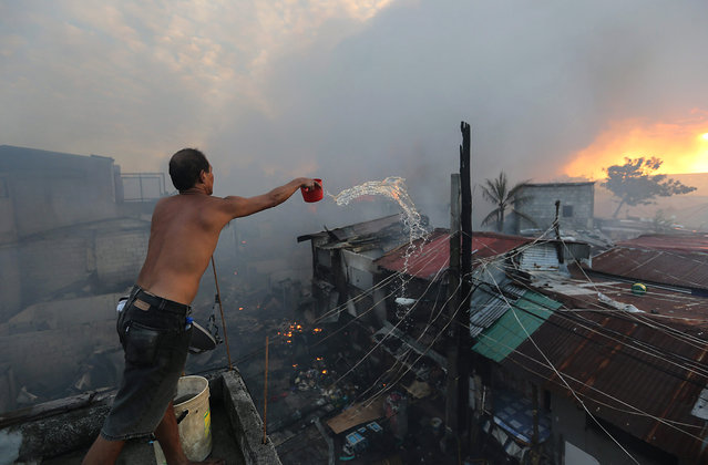Filipino, Fil Binay (L) battles to contain a fire in Mandaluyong City, east of Manila, Philippines, 25 November 2015. The cause of the fire which reached the general alarm is still unknown. (Photo by Mark R. Cristino/EPA)