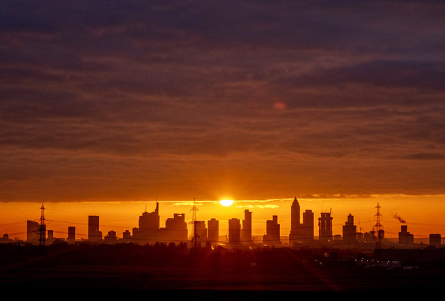 The sun rises over the buildings of the banking district in Frankfurt, Germany, Friday, November 20, 2020. (Photo by Michael Probst/AP Photo)