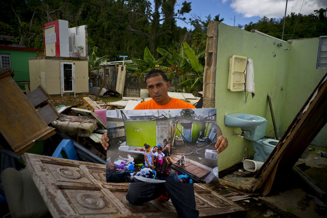"""Arden Dragoni holds a printed photo taken on October 5, 2017 that shows him with his wife Sindy, three children and dog Max, amid the remains of his home that was destroyed by Hurricane Maria, as he stands at the same spot where his home remains in shambles in Toa Baja, Puerto Rico, May 28, 2018. The unemployed construction worker and security guard is currently separated from his family while his wife and his children live in a FEMA subsidized apartment, and he lives with his father. """"The hurricane brought us many calamities but my lesson was to value my family from my heart"""", said Dragoni. (Photo by Ramon Espinosa/AP Photo)"""