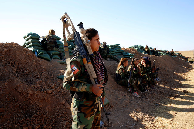 An Iranian-Kurdish female fighter stands behind a sand berm during a battle with Islamic State militants in Bashiqa, near Mosul, Iraq on November 3, 2016. (Photo by Ahmed Jadallah/Reuters)