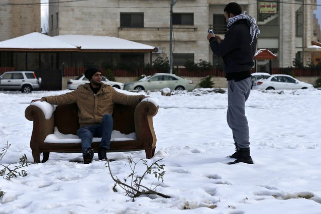 People pose for pictures after a heavy snowstorm in Amman January 11, 2015. A storm buffeted the Middle East with blizzards, rain and strong winds, keeping people at home across much of the region and raising concerns for Syrian refugees facing freezing temperatures in flimsy shelters. (Photo by Muhammad Hamed/Reuters)