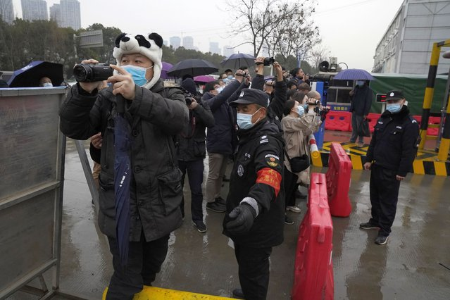 Security personnel block journalists after the World Health Organization team arrive at the Baishazhou wholesale market on the third day of field visit in Wuhan in central China's Hubei province on Sunday, January 31, 2021. WHO says the team plans to visit hospitals, markets and laboratories in a politically charged mission as China seeks to avoid blame for alleged early missteps. A single visit by scientists is unlikely to confirm the virus's origins. (Photo by Ng Han Guan/AP Photo)