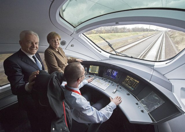 German Chancellor Angela Merkel gestures besides Ruediger Grube, CEO of Deutsche Bahn AG, center behind train driver Stefan Baumgart, front, in the ICE driver's cab during the opening of the new high-speed rail line between Erfurt and Halle/Leipzig near Leipzig, Germany, Wednesday, December 9, 2015. (Photo by Jens Meyer/AP Photo)