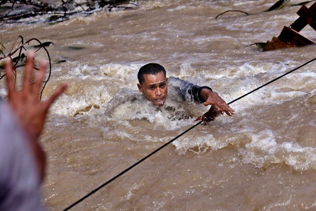 A rescuer uses a rope to cross a swollen river as he and his unit search for victims of a landslide triggered by Tuesday's earthquake in Serempah, Aceh province, Indonesia, on July 5, 2013. The death toll from an earthquake has reached 30, and police and soldiers are searching the debris for another 12 people believed missing. (Photo by Binsar Bakkara/Associated Press)