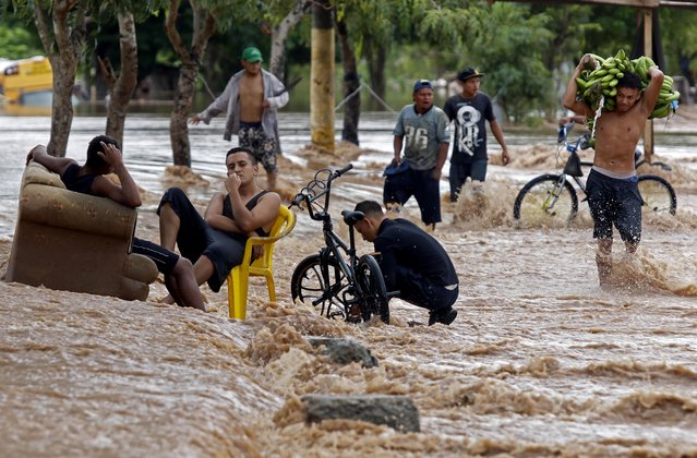 """A yougster carries bananas as he wades near men sitting at a flooded street in El Progreso, department of Yoro, Honduras on November 18, 2020, after the passage of Hurricane Iota, now downgraded to Tropical Storm. Storm Iota, which made landfall in Nicaragua as a """"catastrophic"""" Category 5 hurricane Monday, killed at least ten people as it smashed homes, uprooted trees and swamped roads during its destructive advance across Central America. (Photo AFP Photo/Stringer)"""