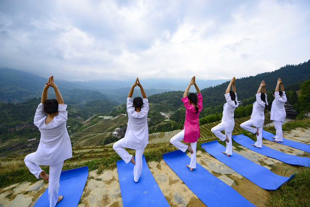 People practice yoga by the Longji terrace fields in Longsheng County, south China's Guangxi Zhuang Autonomous Region, June 21, 2018. The UN General Assembly declared June 21 as the International Yoga Day in 2014. (Xinhua/Pan Zhixiang via Getty Images)