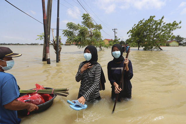 Indonesian men carry their belongings as they wade through the water at a flooded neighborhood following heavy rains in Bekasi, Indonesia, Monday, February 22, 2021. Thousands of residents are being evacuated on the outskirts of Indonesia's capital amid flooding after the Citarum River embankment broke. (Photo by Achmad Ibrahim/AP Photo)